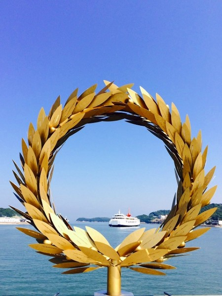 「オリーブの島」小豆島土庄港のシンボル的なアート作品。金色に光り輝く葉には、島の子ども達が寄せた「海へのメッセージ」が刻まれ、海を渡る人々を温かく見守ってくれます。日が暮れるとオリーブの実がライトアップされ、島のゆったりした夜を楽しめるスポットになります。作者はチェ・ジョンファ